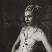 image of gothic female  - Freaky young female model in vintage clothing wearing corset with golden decoration - JPG
