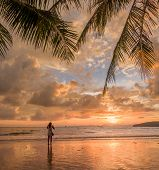 Woman taking pictures of the sunset on the beach of Ao Nang in Krabi Thailand