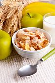 Sweet cornflakes in ceramic bowl, fruits and glass with milk on napkin, on color wooden background
