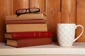 Pile of books with cup and glasses on tabletop and wooden background