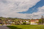 Picturesque Swiss Mountain Village With Cemetery And Cloudscape Background