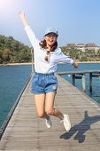 Portrait Of Young Beautiful Woman Jumping With Happy Emotion On Wood Piers At Sea Side Use For Peopl