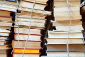 foto of bookworm  - The old dusty books which are tied up by a cord put by a hill - JPG