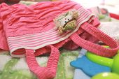Little girl's pink dress lying on bed with toys and blanket