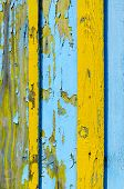 Fragment Of Wooden Fence With Cracked Yellow And Blue Paint