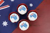 image of red velvet cake  - Happy Australia Day January 26 party food with red velvet cupcakes and Australian maps rice paper toppers on dark red and blue vintage rustic recycled wood background - JPG