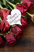 Happy Valentine's Day Red Roses On Dark Recycled Wood Background With Greeting On Heart Shape Gift T