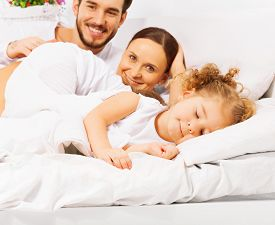 pic of laying-in-bed  - Happy parents with adorable daughter sleeping in front in white pajamas lay on bed  together in the morning - JPG