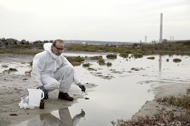 foto of groundwater  - Worker in a protective suit examining pollution in the water at the industry - JPG