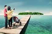 foto of jetties  - Rear view of two parents standing on the jetty with their baby in the stroller looking at tropical island - JPG