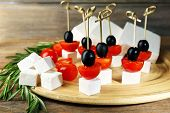 stock photo of trays  - Cheese canapes with cherry tomatoes and olives on wooden tray close up - JPG