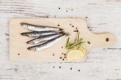 image of peppercorns  - Delicious fresh sardines on wooden kitchen board with lemon rosemary and colorful peppercorns on wooden background - JPG