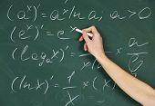 foto of formulas  - Female hand writing formulas on blackboard with chalk - JPG