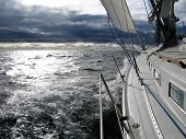 image of windy  - Ongoing sailing in windy conditions looking forward towards dark clouds with the sun shining through - JPG