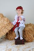 foto of haystack  - Ukrainian girl in national dress and jeans sitting on a haystack legs on economic books - JPG