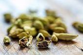 stock photo of cardamom  - Green cardamom grains on an old table close - JPG