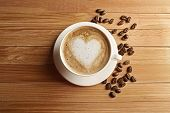 foto of latte  - Cup of coffee latte art with grains on wooden table - JPG