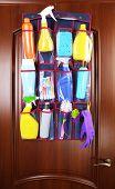 foto of household  - Household chemicals in holder hanging on wooden door background - JPG