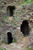 stock photo of fortified wall  - View of caves inside castle walls of Koporye castle - JPG