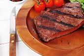 pic of lunch  - lunch of fresh rich juicy grilled beef meat steak fillet with marks on wooden plate over white table served with vegetable salad and cutlery - JPG