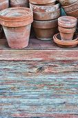 picture of paint pot  - Old clay flower pots on a rough wooden table with faded paint - JPG