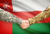 picture of oman  - Soldiers shaking hands with flag on background  - JPG