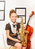 pic of cello  - Happy girl in school uniform dress with alto saxophone sitting near the cello indoors - JPG