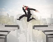 stock photo of gap  - Energetic business man jumping over a bridge with gap concept - JPG