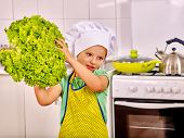 stock photo of pinafore  - Child holding vegetable at kitchen - JPG