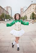 stock photo of wig  - Young woman in irish dance dress and wig posing outdoor - JPG