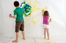 stock photo of ten years old  - Two young children a ten year old boy and three year old girl freehand painting on a wall with colorful acrylic paints creating an abstract design viewed from behind - JPG