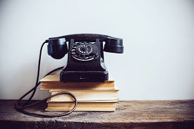 foto of vintage antique book  - Black vintage rotary phone and books on rustic wooden table - JPG