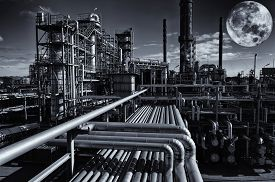 stock photo of refinery  - oil and gas refinery under a large full moon - JPG
