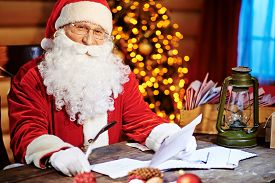 image of letters to santa claus  - Santa Claus looking at camera while reading Christmas letter - JPG