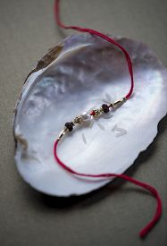 stock photo of rakhi  - A thin red Rakhi with pearl in a sea shell - JPG
