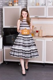 stock photo of ordinary woman  - Happy ordinary woman with pan at her kitchen - JPG
