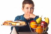 picture of healthy food  - boy thinking over a healthy snack or a dessert - JPG
