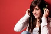 Young Girl Listening Music With Headphones On A Red Wall