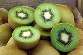 Green kiwi fruit and some cut ones