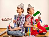 Repair home women holding painting tools roller for wallpaper and paint bank for wall. Happy girls w poster