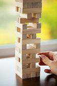 The tower from wooden blocks and mans hand take one block poster