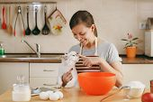 A Young Beautiful Happy Woman With A White Persian Cat Prepares Dough For Christmas Cakes With Table poster
