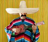 Mexican man serape poncho sombrero playing guitar typical Mexico