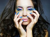 Photo of a young beautiful woman with bright makeup and manicure