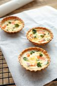 Tasty salmon tartlets on parchment poster