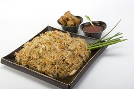 pic of lumpia  - Pancit on a ceramic dish with egg rolls and sweet and sour sauce - JPG