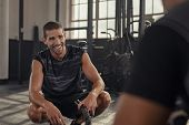 Smiling young man sitting on his toes taking a break after doing fitness workout while talking with  poster