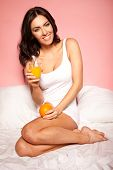 Smiling beautiful brunette woman curled up on her unmade bed with a glass of orange juice and a fresh orange for breakfast