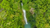 Aerial Top View Jungle Waterfall In A Tropical Forest Surrounded By Green Vegetation. Mantayupan Fal poster