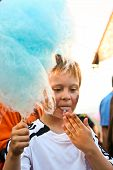picture of finger-licking  - boy enjoys cotton candy at the fair and licks his hands - JPG